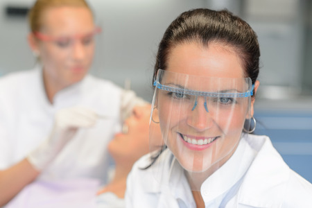 checkup: Professional dentist with protective glasses patient woman dental checkup Stock Photo