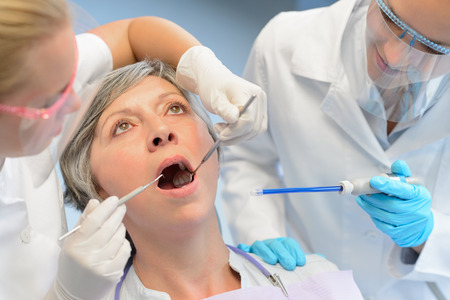 Dental check elderly woman patient professional dentist team open mouth photo