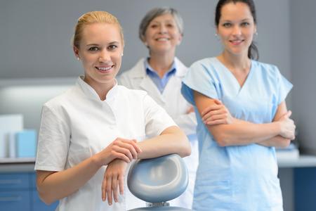 Three professional dentist woman team standing dental surgery looking camera