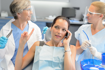 Busy businesswoman at dental surgery calling on phone dentists waiting Zdjęcie Seryjne