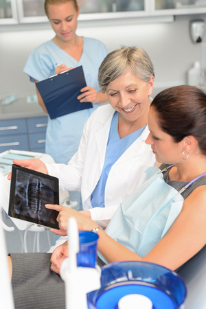 Woman patient at dental surgery dentist show teeth xray tablet