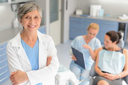 Professional dentist woman patient consultation with assistant at dental surgery
