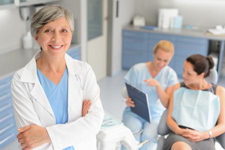 Professionele tandarts vrouw patiënt overleg met assistent bij kaakchirurgie