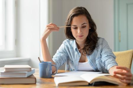 adolescentes estudiando: Adolescente que estudia el libro de lectura en casa para concentrarse mirando hacia abajo