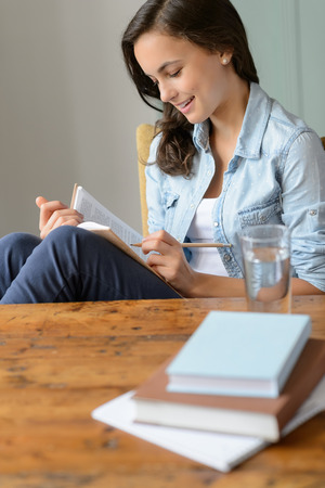 Teenage girl student reading book at home sitting wooden table photo