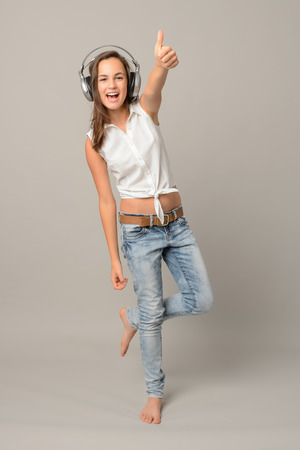 Girl enjoy listening music and dance thumb-up full length on gray photo