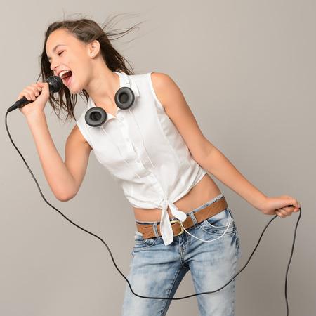 Singing teenage girl with microphone karaoke music on gray background