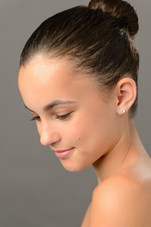 Teenage girl purity  skin beauty face looking down on gray photo