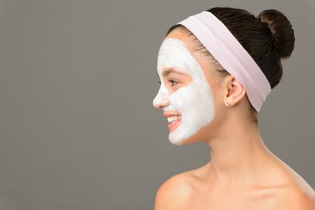 Teenage girl cosmetics mask beauty looking away on gray background photo