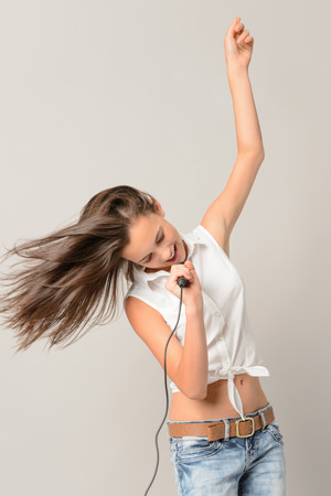 Dancing teenage girl singing with microphone blowing hair on gray background photo
