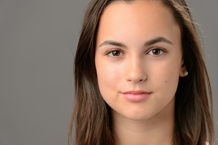 one teenager: Teenage girl beauty face cosmetics brunette close-up on gray