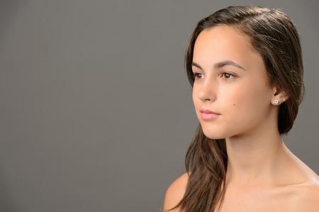 face side: Skin beauty teenage girl brunette looking away on gray background