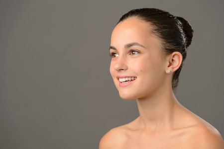 bare shoulders: Teenage girl bare shoulders skin cosmetics beauty smiling on gray background Stock Photo