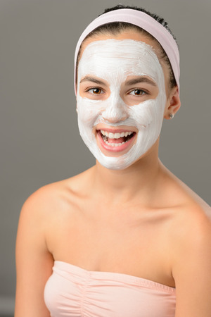 Body care young woman white facial mask smiling on gray background photo