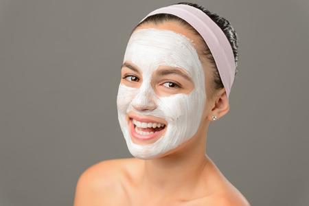 bare shoulders: Smiling young girl face mask bare shoulders on gray background
