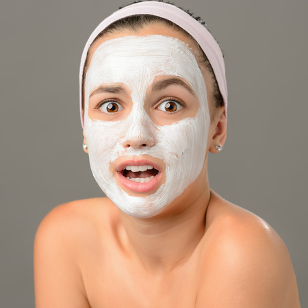 Surprised teenage girl looking camera face mask on gray background photo