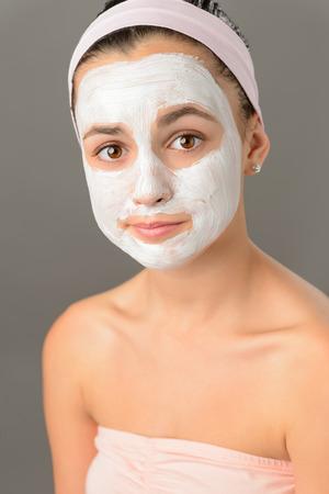 Sad teenage girl face mask skin beauty on gray background photo