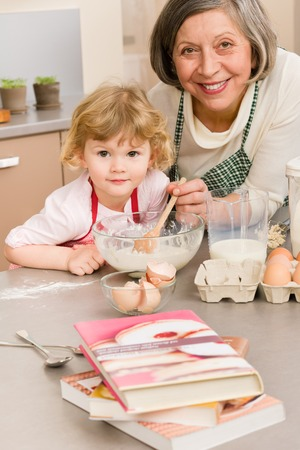 Child girl and grandmother baking cake stir dough photo