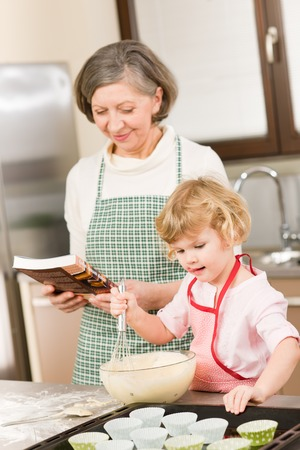 Funny little girl baking cupcake with grandmother hold whisk photo