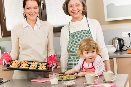 Family women baking cupcakes in kitchen grandmother, mother and granddaughter Stock Photo - 30413560