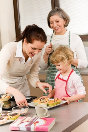 baking tray: Grandmother, mother and child girl making cupcakes in kitchen Stock Photo