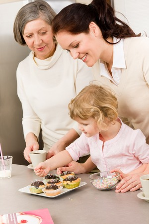 mother and daughter decorating cupcakes sprinkles happy together at home photo