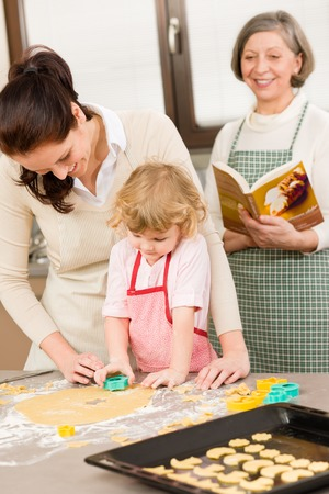 Little girl with mother cutting out cookies in kitchen Stock Photo - 30413612
