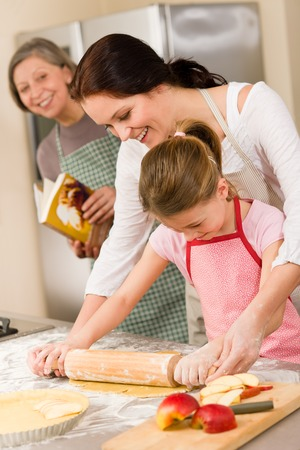 Mother and daughter making apple pie together grandmother check recipe Stock Photo - 30413616