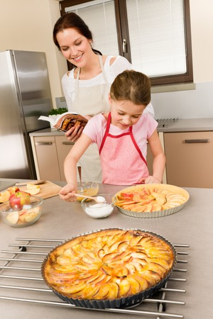 Mother and daughter making apple pie follow recipe from cookbook photo