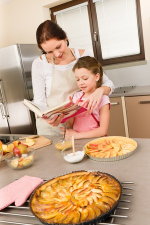 Apple pie mother and daughter follow recipe from baking cookbook Stock Photo - 30413620