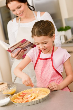 Young girl prepare home tart with mother adding sugar photo