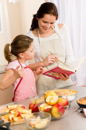 Apple pie mother and daughter follow recipe from baking cookbook Stock Photo - 30413622