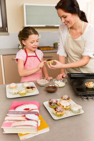 Mother and daughter decorating cupcakes sprinkles happy together at home Stock Photo - 30413623