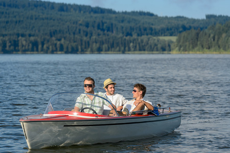 lipno: Young men sitting in motorboat in scenic landscape Stock Photo