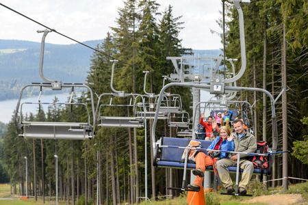 Waving young people sitting on chairlift going through forest photo