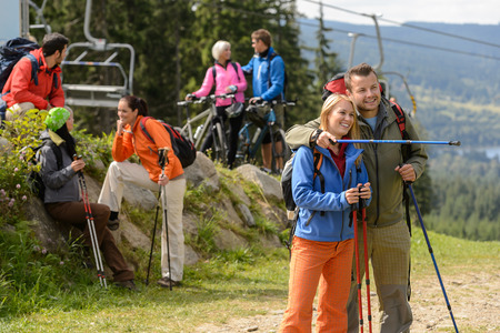 Young hikers and cyclists talking and watching landscape photo