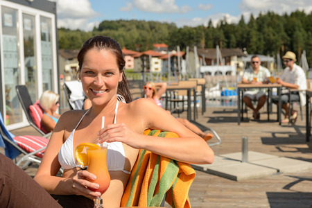 lipno: Woman with wet hair drinking cocktail sitting at beach bar