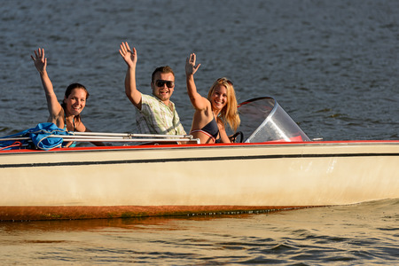 lipno: Young people waving from motorboat enjoying summer break