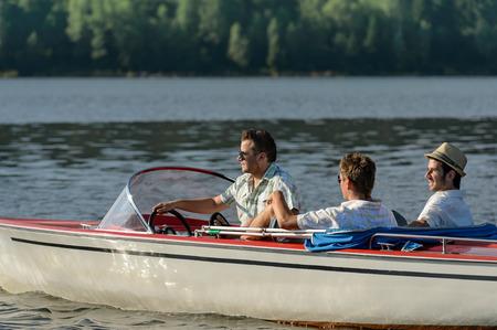 Young men driving speed boat enjoying sunshine photo