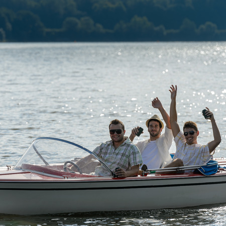 lipno: Cheerful young men party drinking beer on speed boat
