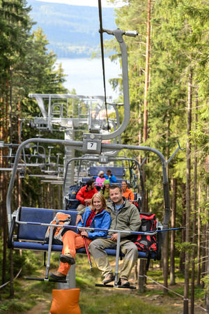 Chairlift going through forest with young people photo