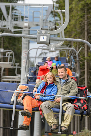 Lovely hiker couple sitting together on chairlift photo