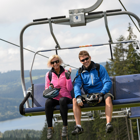 lipno: Young smiling couple sitting on chairlift