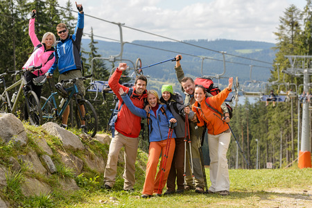 Cheering hikers with raised arms at peak of the mountain photo
