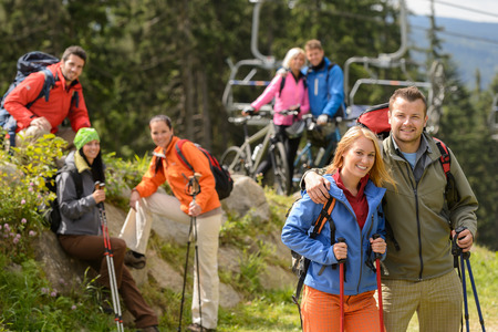 Smiling hikers and cyclists posing peak of the mountain photo