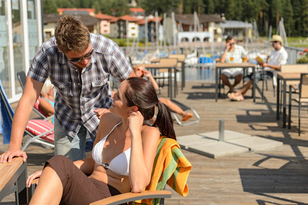 Young couple talking at bar beside beach summer terrace photo