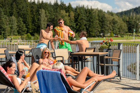 Young group of friends enjoying summertime drinking and sunbathing photo