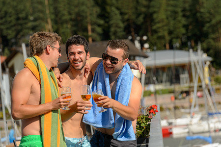 lipno: Young guys toasting with beer enjoying summer in swimsuits Stock Photo
