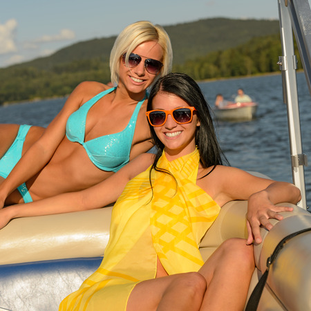 Young happy women sunbathing on boat enjoying summer photo
