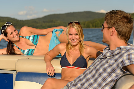 lipno: Sunbathing young friends lying and talking on yacht summer